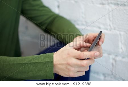 people, technology and internet concept - close up of male hands with smartphone at school