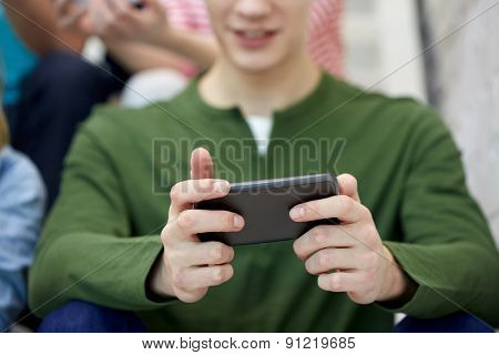 people, technology and internet concept - close up of young man with smartphone at school