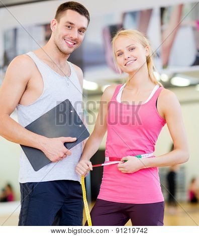 fitness, sport, training, diet, gym and lifestyle concept - two smiling people with clipboard and measure tape in the gym