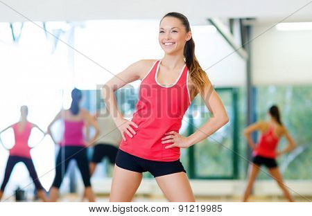 fitness, sport, training, gym and lifestyle concept - smiling trainer working out in the gym