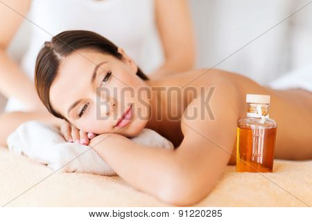 beauty and spa concept - beautiful woman in spa salon getting oil treatment