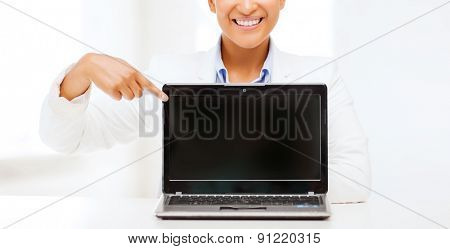 education,business, technology and internet concept - smiling woman with laptop computer
