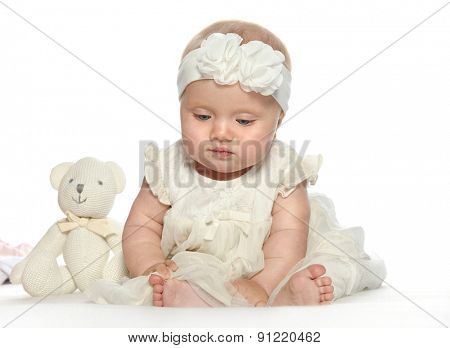 baby girl child sitting down on white blanket white dress fashion portrait face studio shot isolated on white caucasian teddy bear