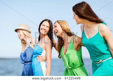 summer holidays and vacation - girls walking on the beach