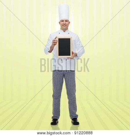 cooking, profession, advertisement and people concept - happy male chef cook showing and holding blank menu chalk board over yellow background