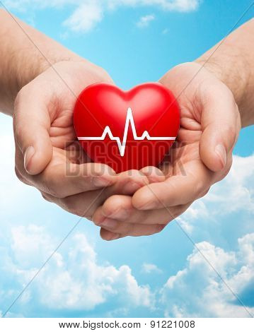 family health, charity and medicine concept - close up of hands holding red heart with cardiogram over blue sky and clouds background