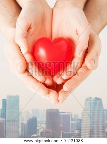 health, love and relationships concept - close up of couple hands with big red heart over city skyscrapers background