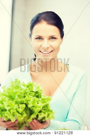 beautiful woman in the kitchen with green salad leaves..