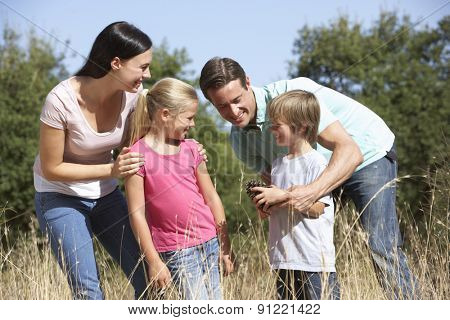 Young Family Walking Through Summer Countryside
