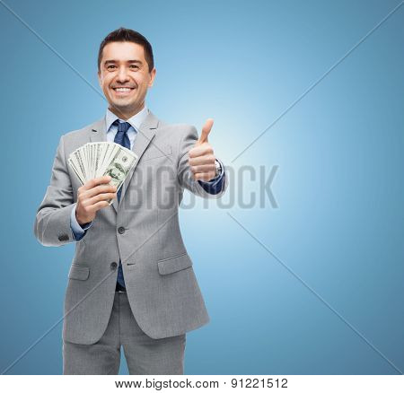 business, people and finances concept - smiling businessman with dollar money showing thumbs up over blue background