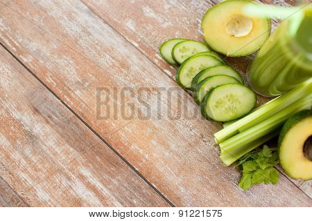 healthy eating, organic food, advertisement and diet concept - close up of fresh green juice glass and vegetables on blank table