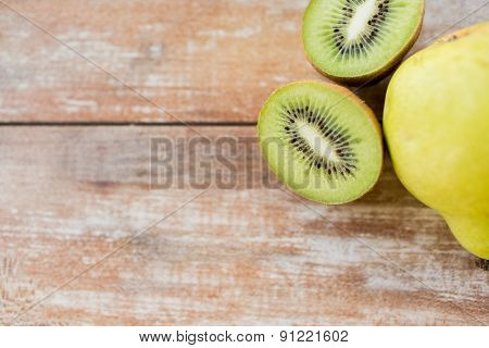 fruits, diet, food and objects concept - close up of ripe kiwi and pear on table