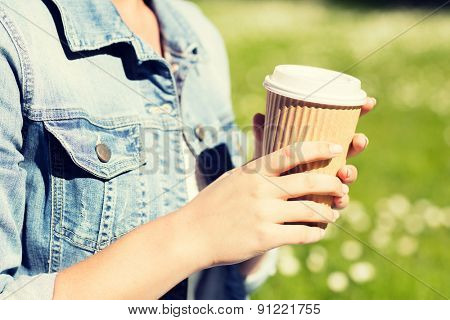 lifestyle, summer vacation, leisure, drinks and people concept - close up of young girl with coffee cup in park
