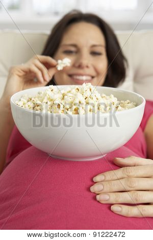 Pregnant Woman Eating Bowl Of Popcorn Sitting On Sofa At Home