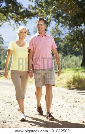 Middle Aged Couple Walking Through Countryside
