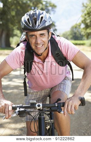 Middle Aged Man Cycling Through Countryside