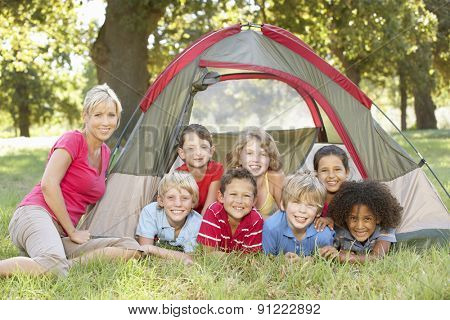 Group Of Children With Mother Having Fun In Tent In Countryside