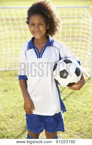 Young Boy Dressed In Soccer Kit Standing By Goal