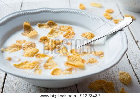 Close up of cup of milk with cornflakes in rustic table