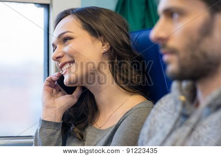 Portrait of a happy young woman talking on telephone whiel travelling on train. She is looking away and out of the window. She is smiling and near her boyfriend.