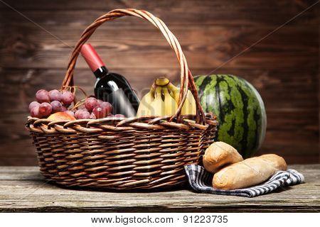 Basket full of fresh fruit, wooden background