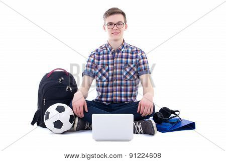 Handsome Teenage Boy Sitting With Laptop, Backpack And Soccer Ball Isolated On White