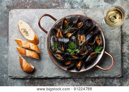 Mussels In Copper Cooking Dish And French Baguette With Herbs On Stone Slate Background
