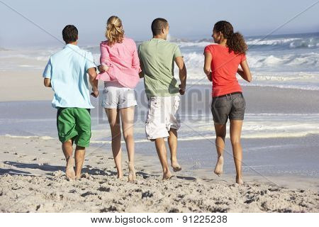 Young Friends Walking Along Beach