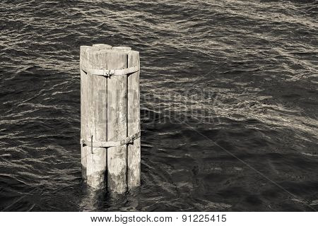 Old Wooden Column Sticks Out Of Water