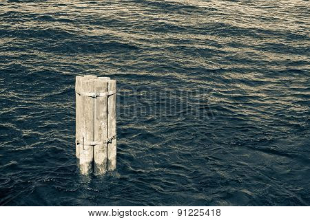 One Old Wooden Column In Water