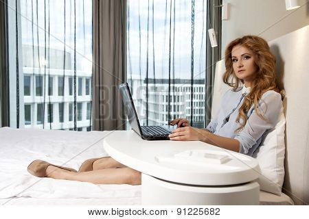 Young adult beauty attractive sexy and sensuality happy pretty blonde businesswoman using laptop while lying on bed in hotel room