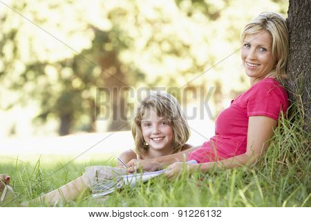 Mother And Daughter Sketching In Countryside Leaning Against Tree