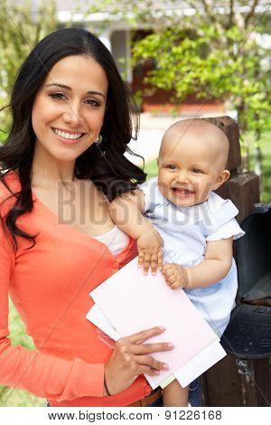 Hispanic Mother And Baby Checking Mailbox