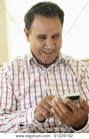Senior Hispanic Man Using Smartphone At Home
