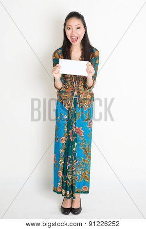 Full length portrait of cheerful Southeast Asian female in batik dress hands holding an envelope standing on plain background.