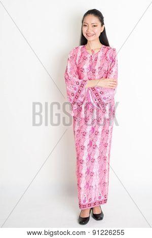 Full body portrait of happy Southeast Asian woman in pink batik dress standing on plain background.