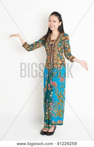 Full length portrait of Southeast Asian woman in batik dress showing welcome gesture standing on plain background.