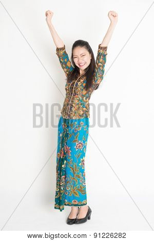 Full length portrait of Southeast Asian female in batik dress arms up and cheering, standing on plain background.