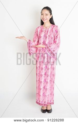 Full body portrait of happy Southeast Asian woman in pink batik dress hands showing something, standing on plain background.