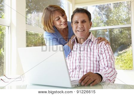 Senior Hispanic Couple In Home Office With Laptop