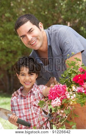 Hispanic Father And Son Working In Garden Tidying Pots