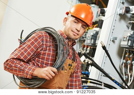 electrician engineer worker with cable in front of fuseboard equipment