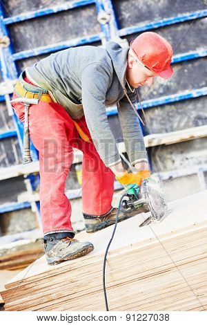 builder carpenter worker with disk saw cutting plywood for falsework construction before concreting at building site