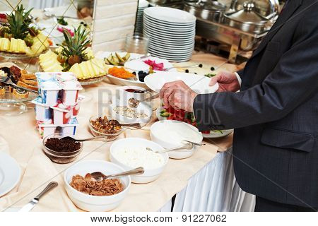 Hotel restaurant catering service. Man with food at morning buffet style smorgasbord breakfast