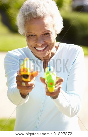 Senior Woman Shooting Water Pistols