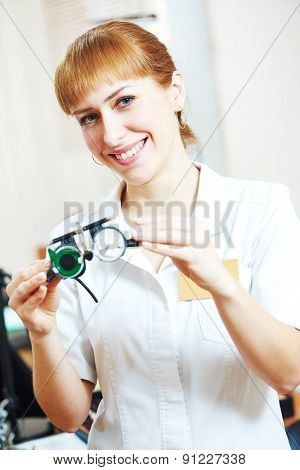 Ophthalmology. portrait of female optometrist optician doctor with test glasses phoropter in eye correction medic clinic