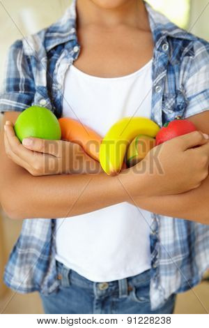 Young girl holding plastic fruit and vegetables