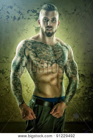 Tattoo unique muscle-building man standing in front of the wall