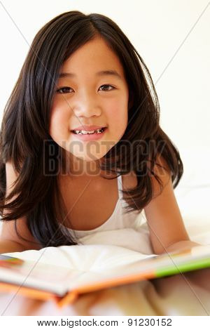 Young Asian girl reading book