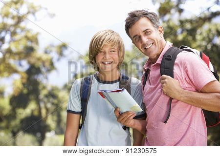 Father And Son Hiking Through Countryside